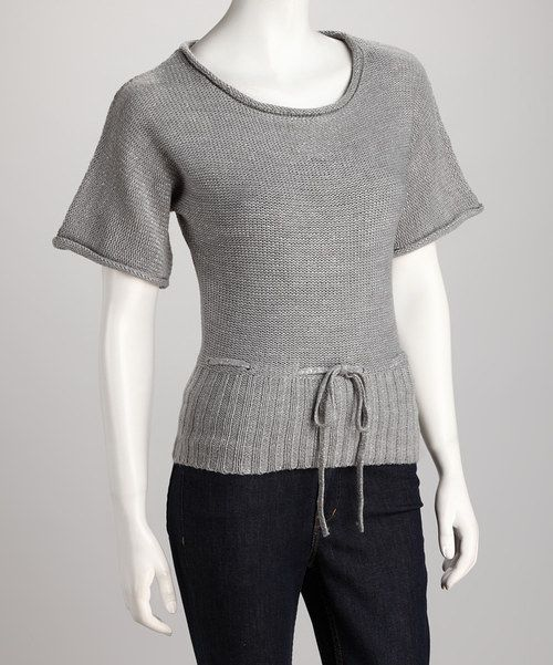 Trendy and timeless, this knit, short-sleeve sweater will stay a closet keeper. Soft shining fabric features a ribbed hem and tie at the lower waist, crafting a look that's simply lovely.Measurements (size S): 24'' long from high point of shoulder to hem55% cotton / 45% acrylicMachine wash; tumble dry