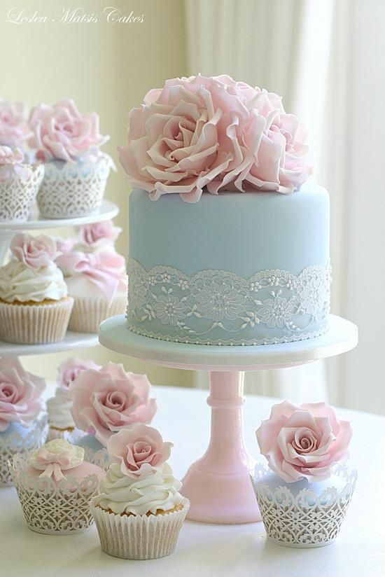 Torta de boda de color azul decorada con cinta de encaje y flores de azúcar de color rosa.