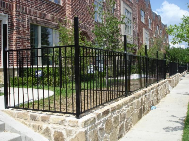 Retaining wall along sidewalk with fence outdoor spaces