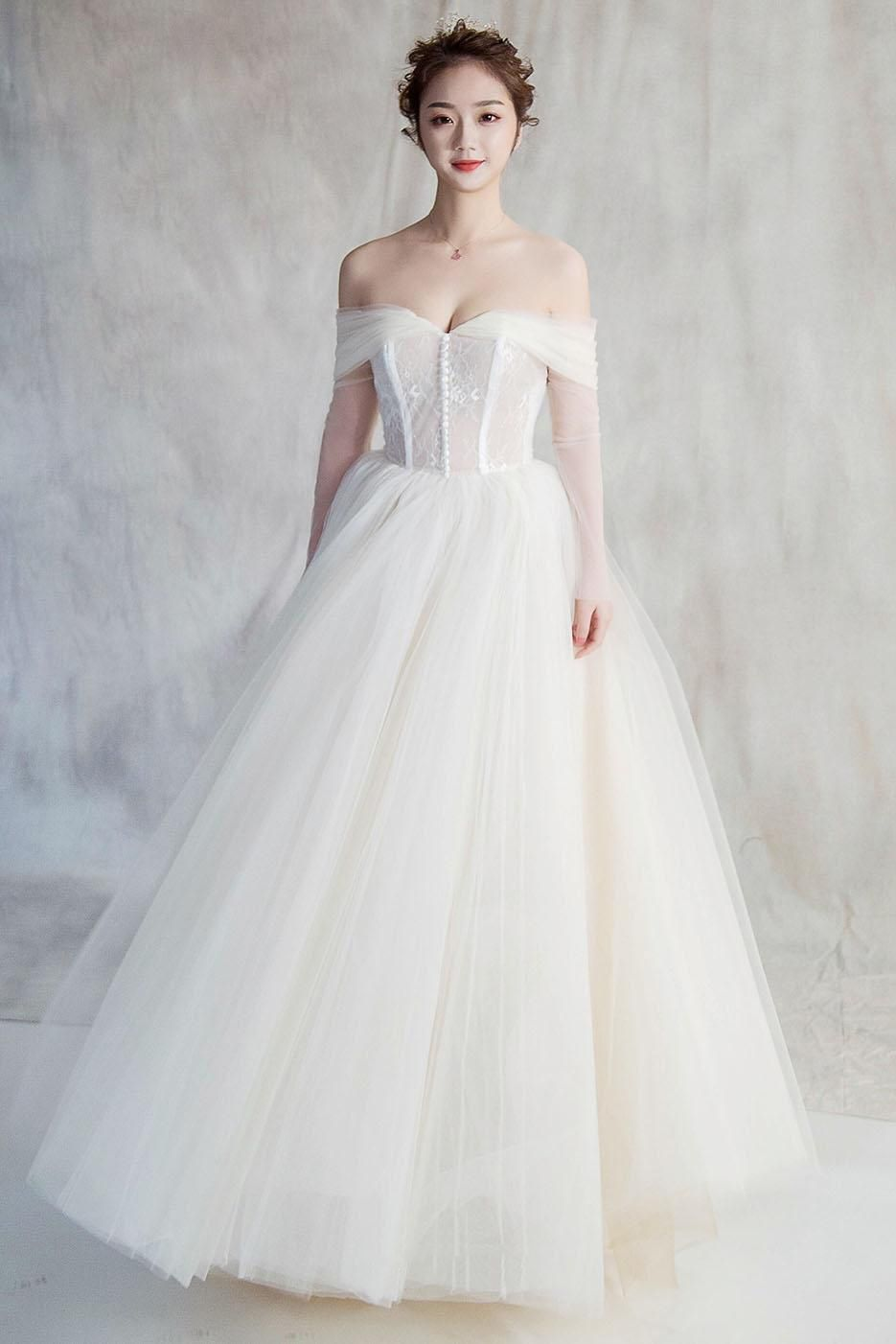 7d56a284466d This lovely long ivory tulle wedding dress featuring demure sheer long  sleeves, elegant off-the-shoulder detail, classic ball gown silhouette, ...