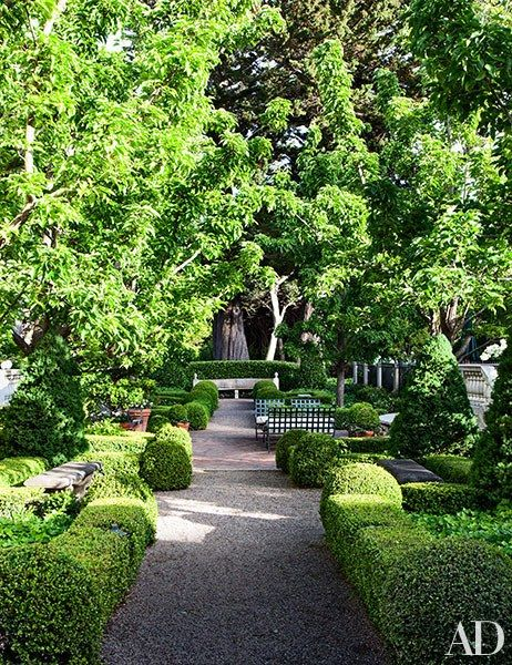 Boxwood hedges border a path in the gardens, which were updated by Strata Landscape Architecture | archdigest.com