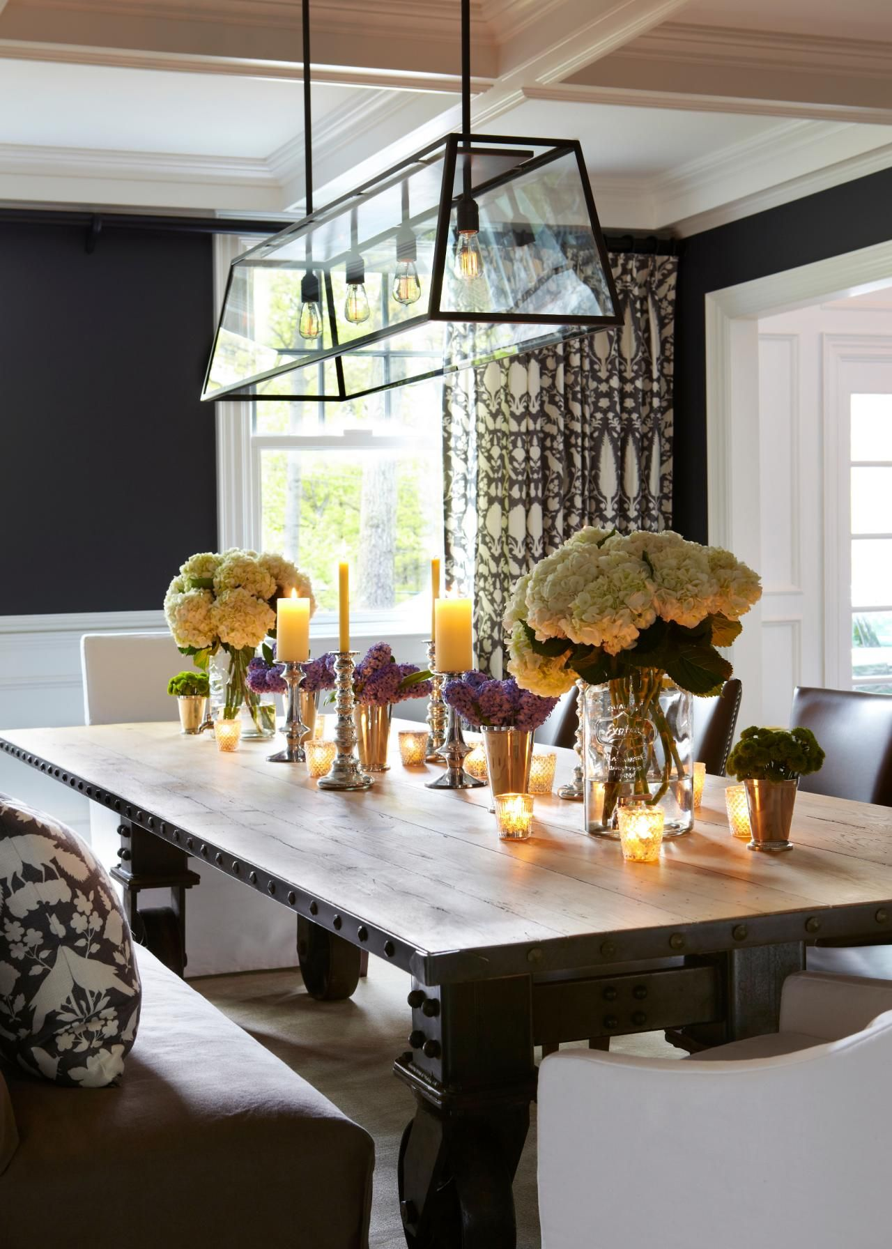A large harvest table is bold focal point in this formal