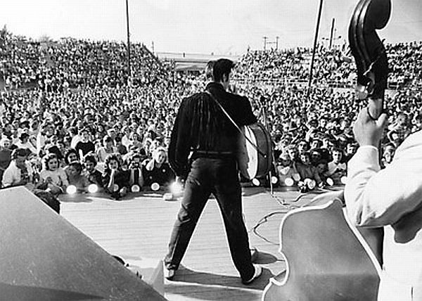 Elvis performing before capacity crowd at the Mississippi-Alabama Fairgrounds, Tupelo, MS, September 26, 1956. Elvis Presley in the mid-1950s, before he became a fully-known national rock 'n roll star, was constantly on the road. During 1955 and 1956, Elvis and his band performed widely, especially in the south, making numerous personal appearances, from high schools to county fairs. His 1955 itinerary, reprinted below, reveals an unyielding schedule of nearly daily performances.