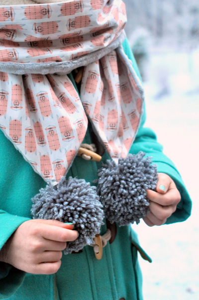 Sew a simple, but adorable winter pom-pom scarf for a little person!  There's no tutorial, but an intermediate seamstress can make it in a heartbeat.  :)  And, there is a link to an easy pom pom tutorial.