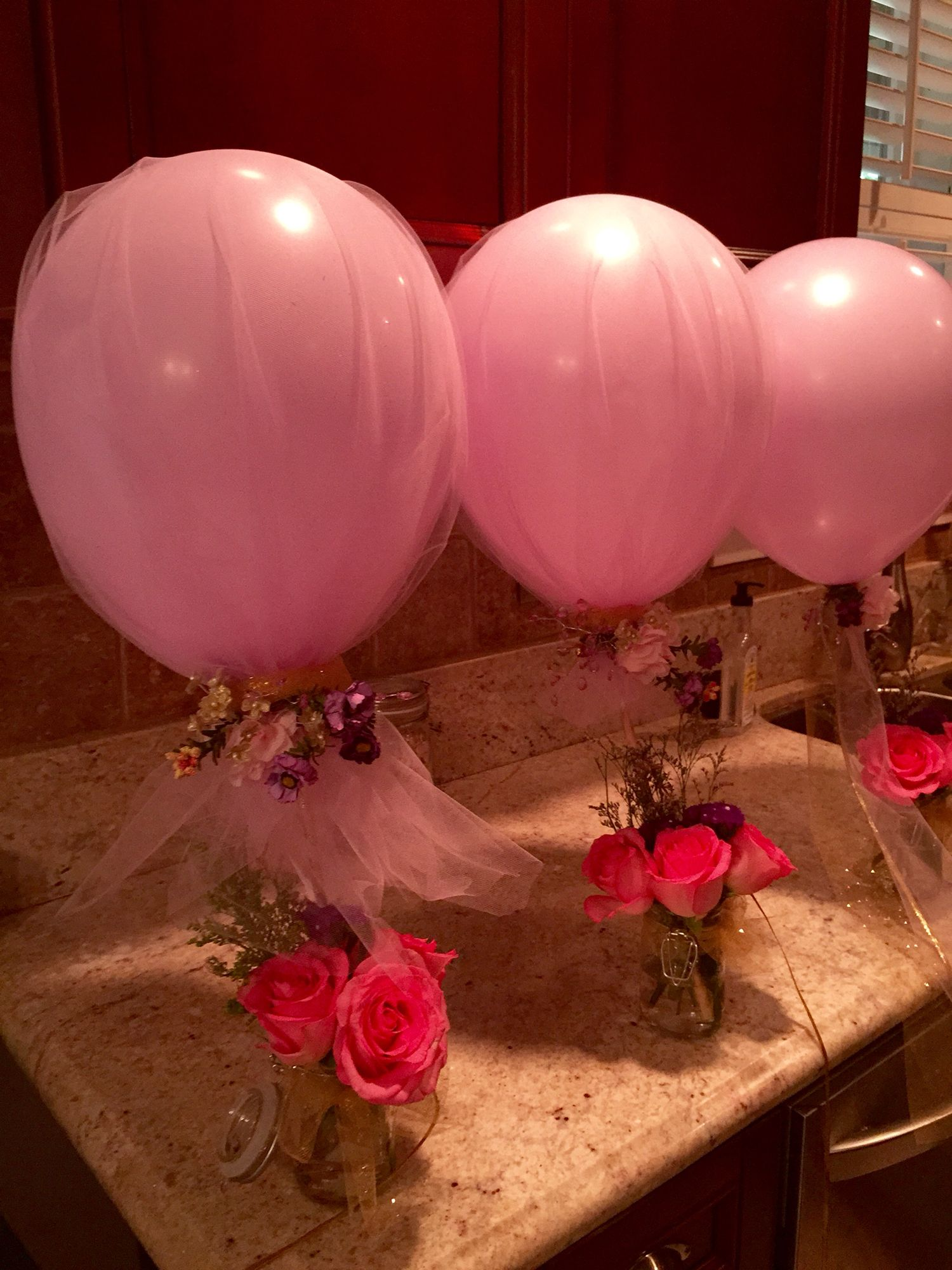Tulle balloons with floral trims on dowels placed in