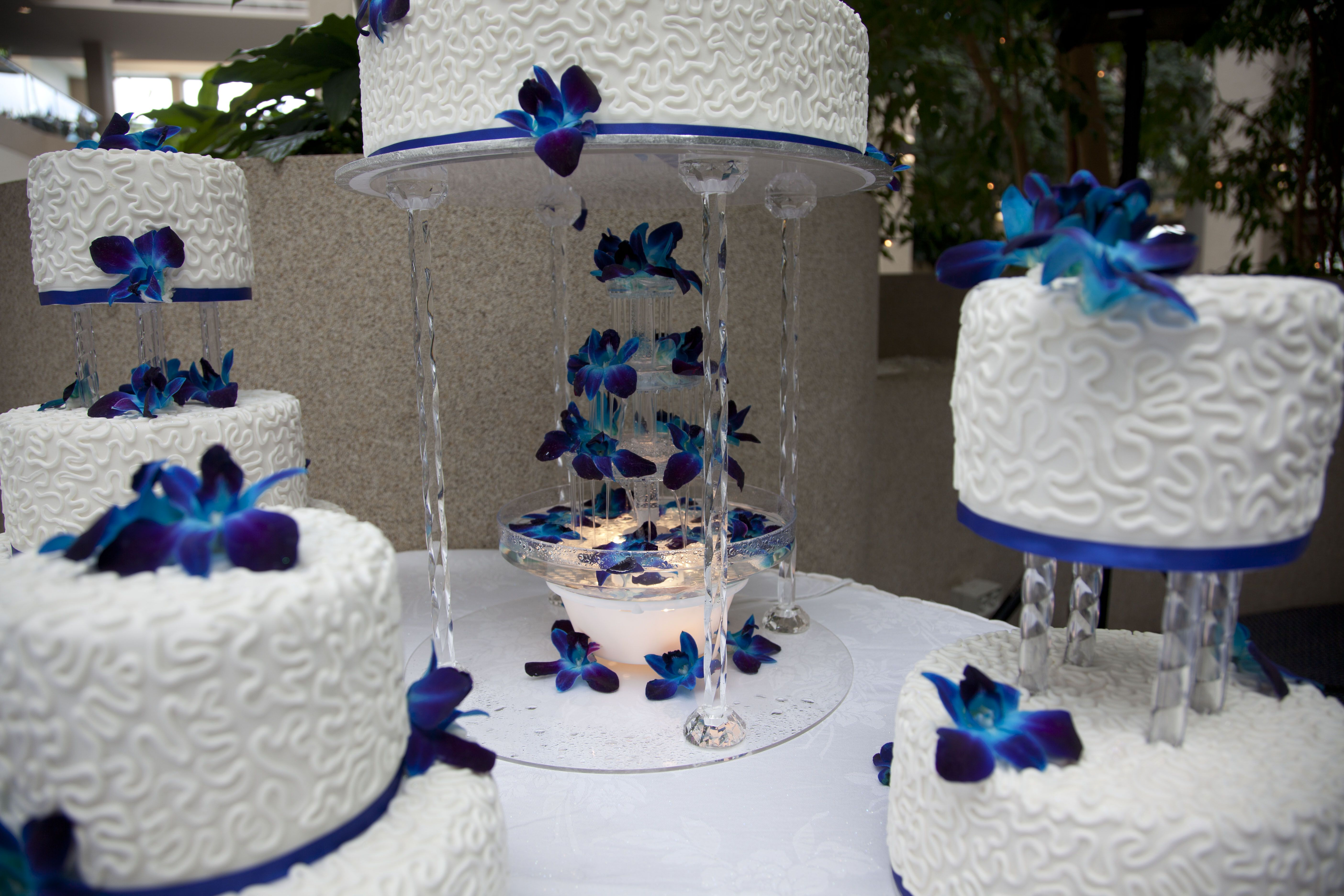 Water Fountain Under The Royal Blue Wedding Cake Decorated With White Chocolate Butter Cream