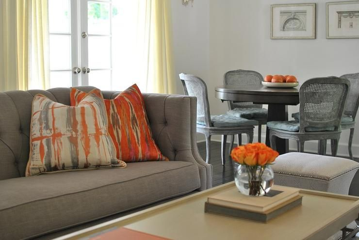 Gray And Orange Living Room Features A Gray Tufted High Back Sofa