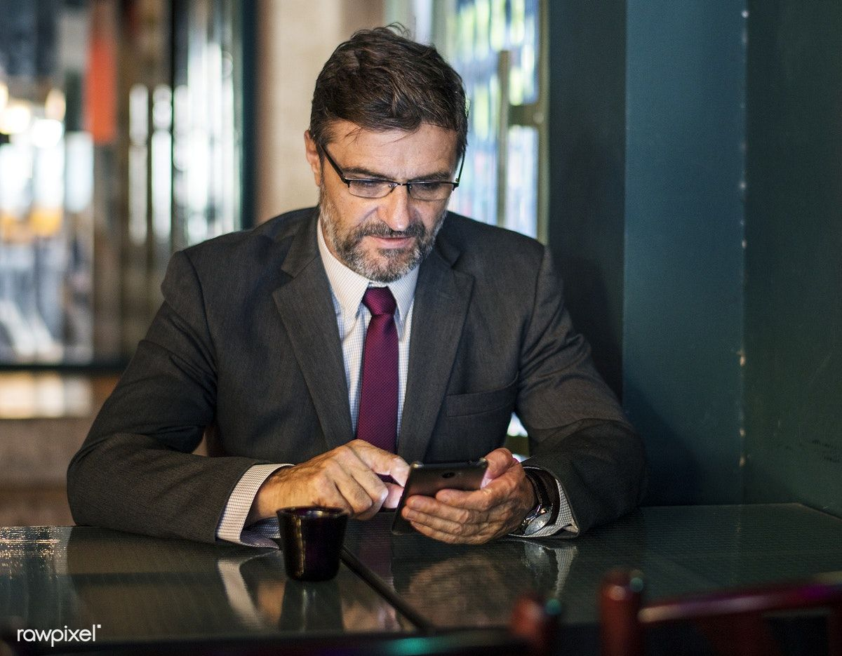 Businessman texting on his mobile phone free image by