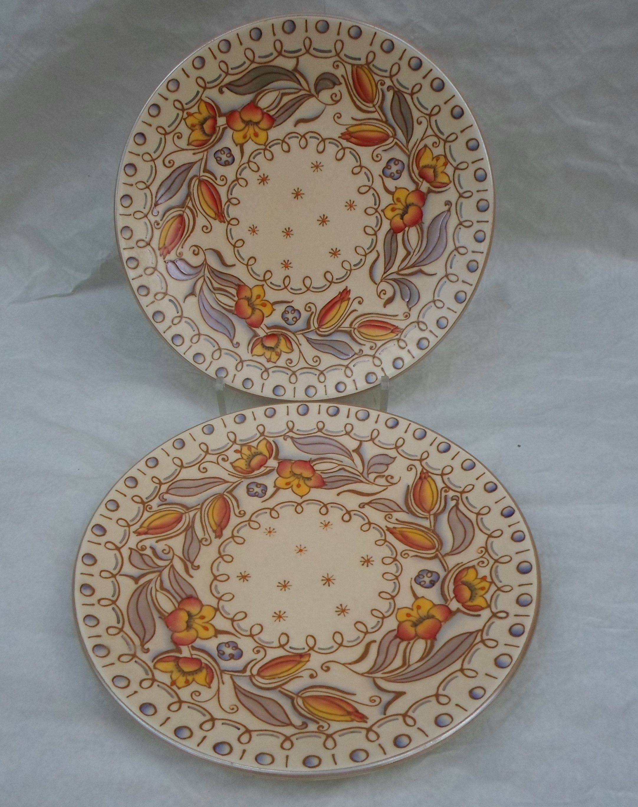 Two 1940s HJ Wood Bursleyware chargers, in the TL95 pattern, designed by Eddie Sambrook (after Charlotte Rhead), having a tube-lined decoration of stylized flowers and leaves on a buff ground, printed and tubed marks to the bases, each 30.5cm diameter