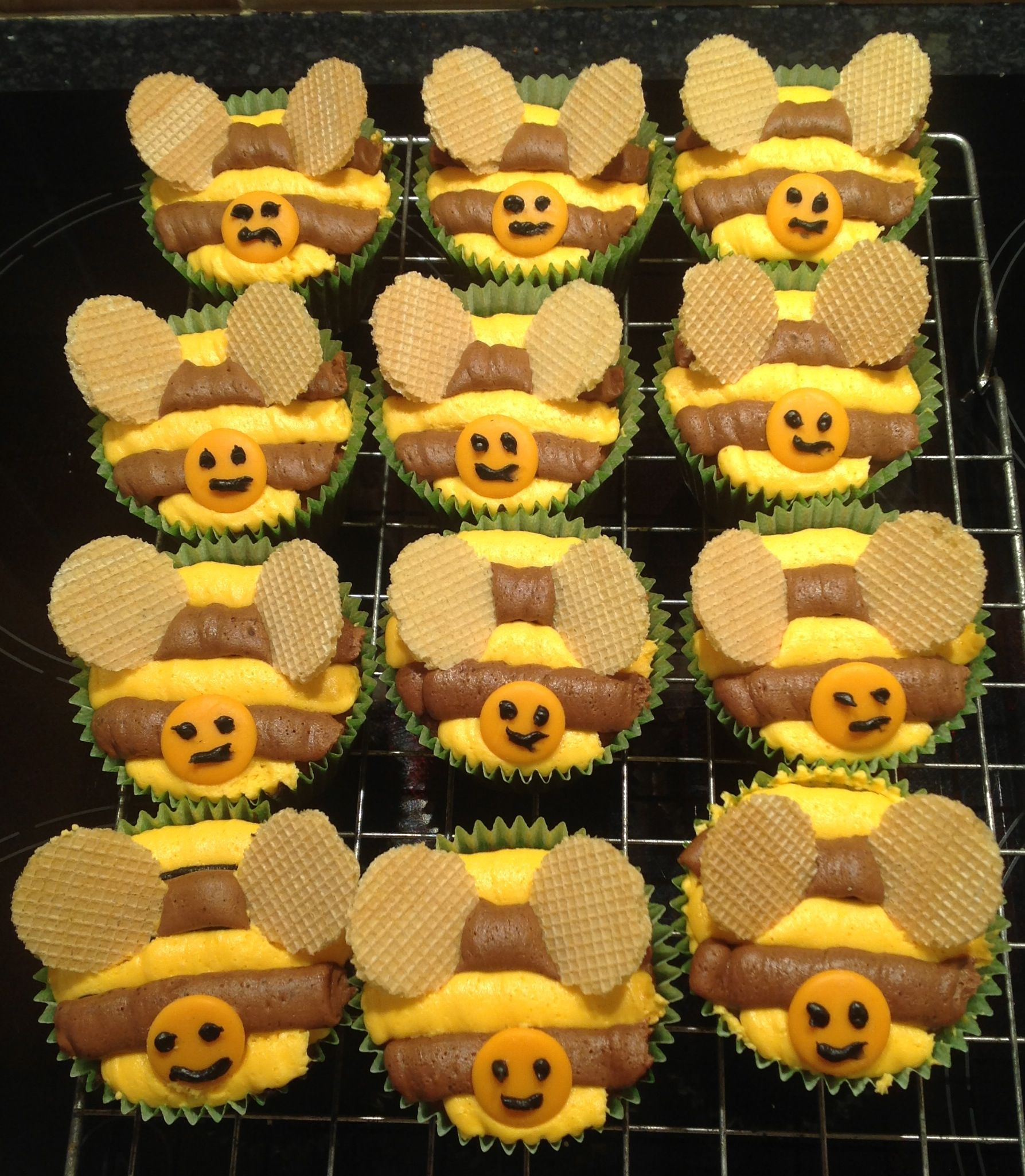 Bee cup cakes - for my dads birthday Yellow and chocolate icing piped in stripes, with orange chocolate buttons for the face, and ice cream wafers for the wings!