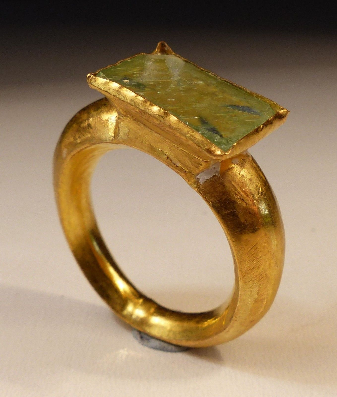 Hollow gold ring having a thick graduated band supporting a square