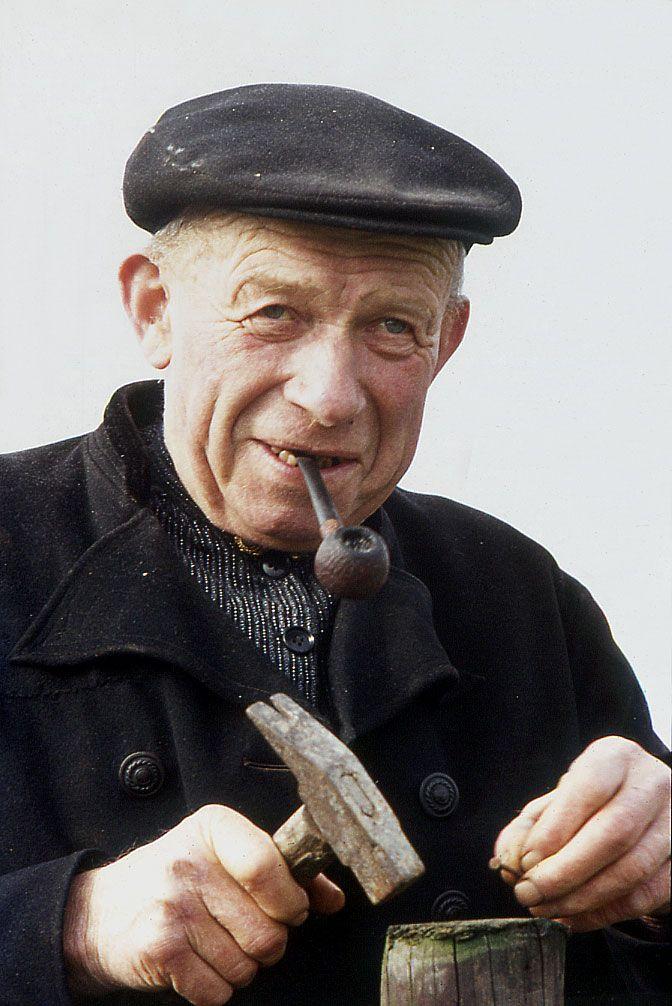 db591177c09 old man - grandpa - hammer - metal smith - golf hat - pipe - wrinkles -  hands - black coat - smile - eyes - guy - dude