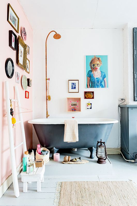 Millennial Pink Wall Filled With Small Portraits Grey Painted Wooden Floors And Blue Claw Foot Tub