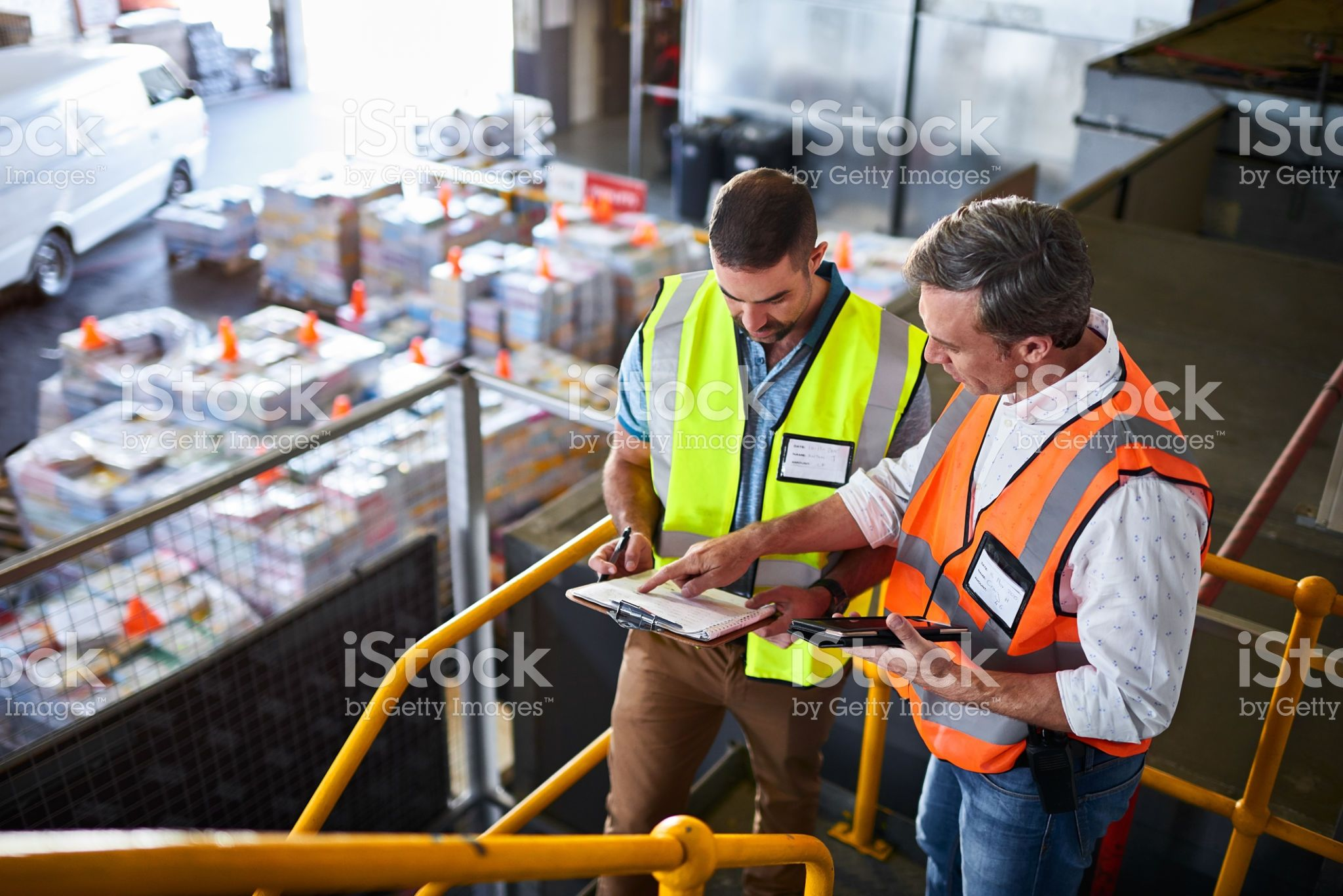Shot Of Two Warehouse Workers Standing On Stairs Using A Digital