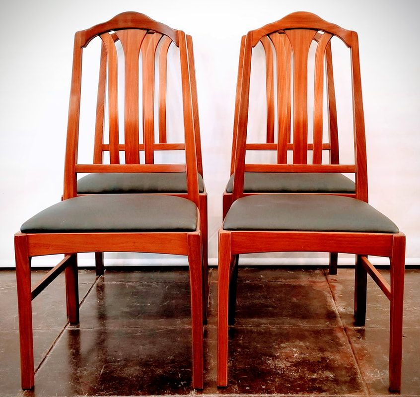 set of four slat back dining chairs with black seats from