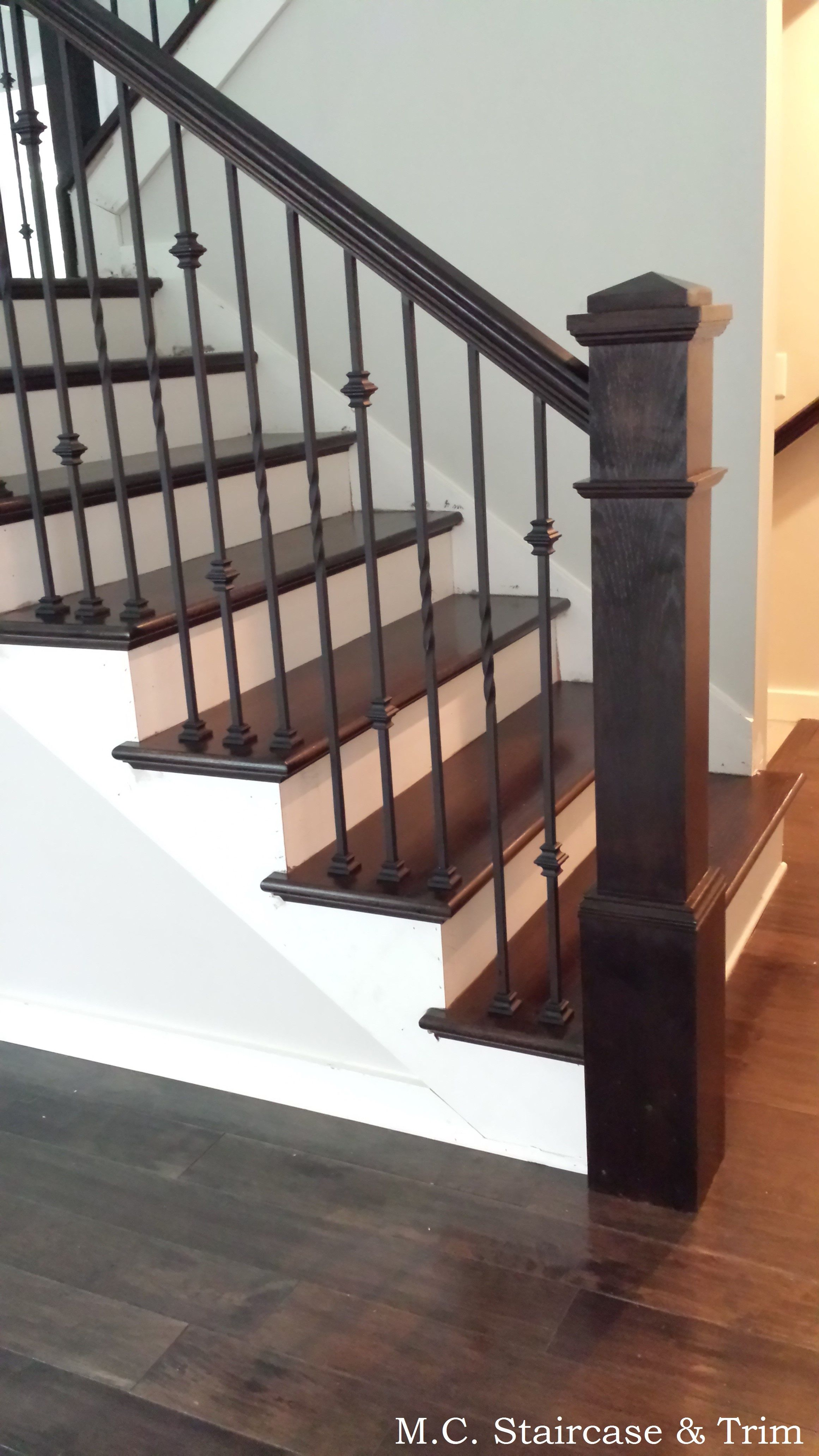 Staircase- wooden railing and wooden balusters. Installation of stained  treads, risers, box newels, handrail, square rosettes and iron balusters.  Iron ...