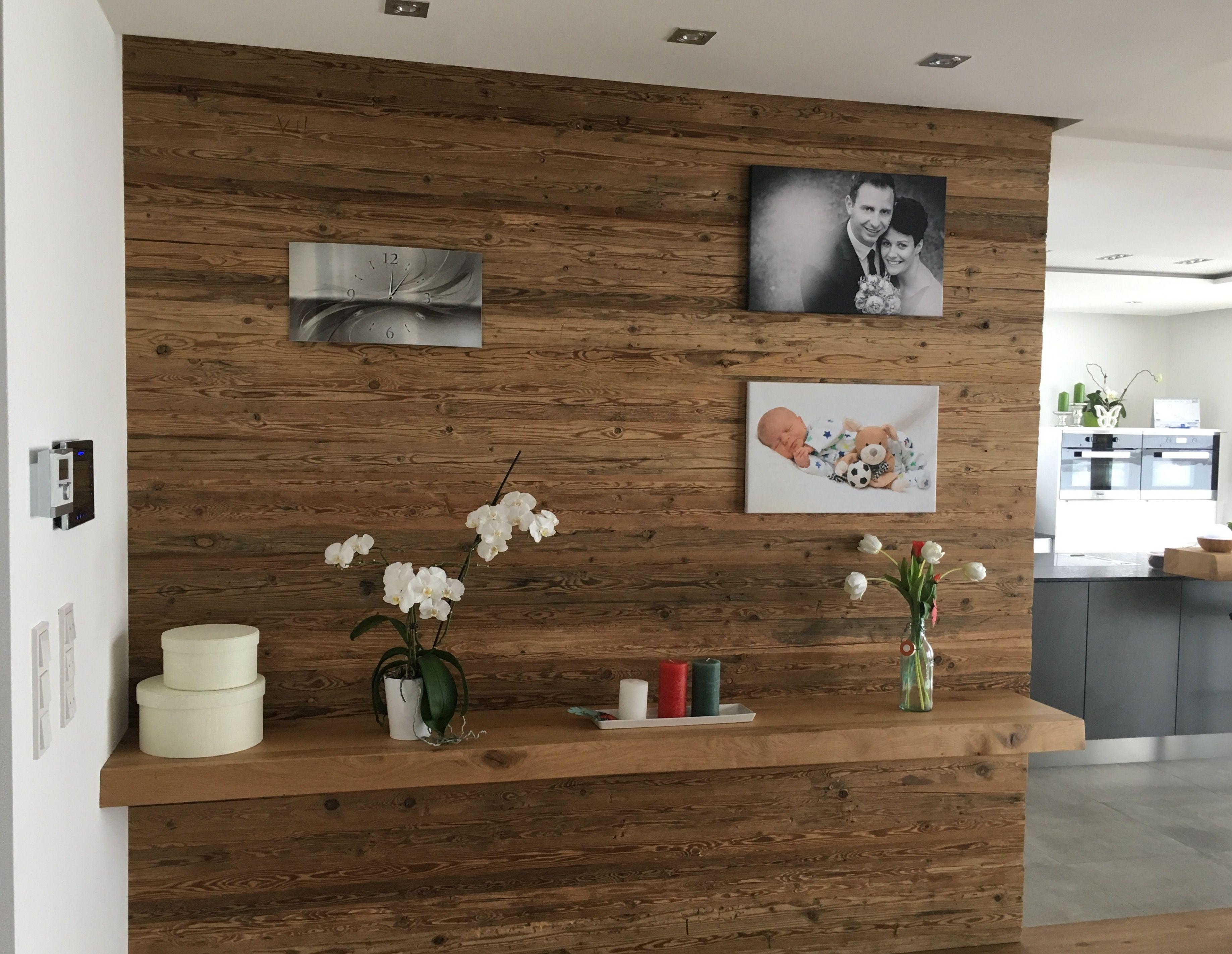 Altholzwand als Blickfang im Esszimmer in einem Einfamilienhaus mit indirekter und direkter Beleuchtung sowie edlem Eicheboard