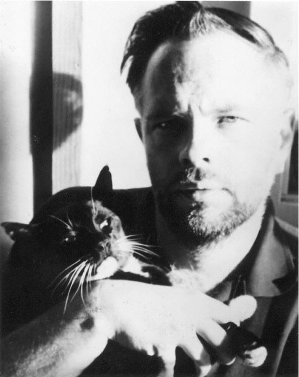 Philip K. Dick with an unhappy looking feline.  Photo by Anne Dick.