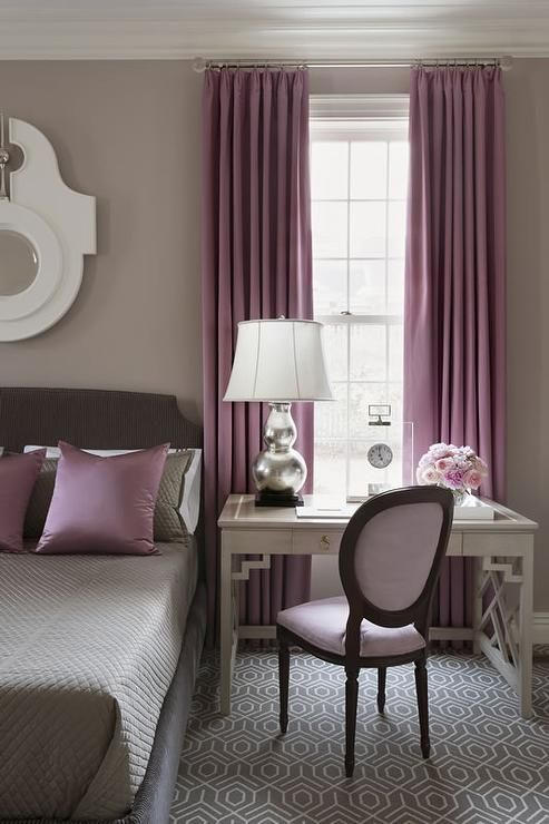 Gray And Purple Bedroom Features Walls Painted Warm Gray Lined With A Gray  Bed Dressed In Gray Bedding And Purple Pillows Next To A Gray Desk As  Nightstand ...
