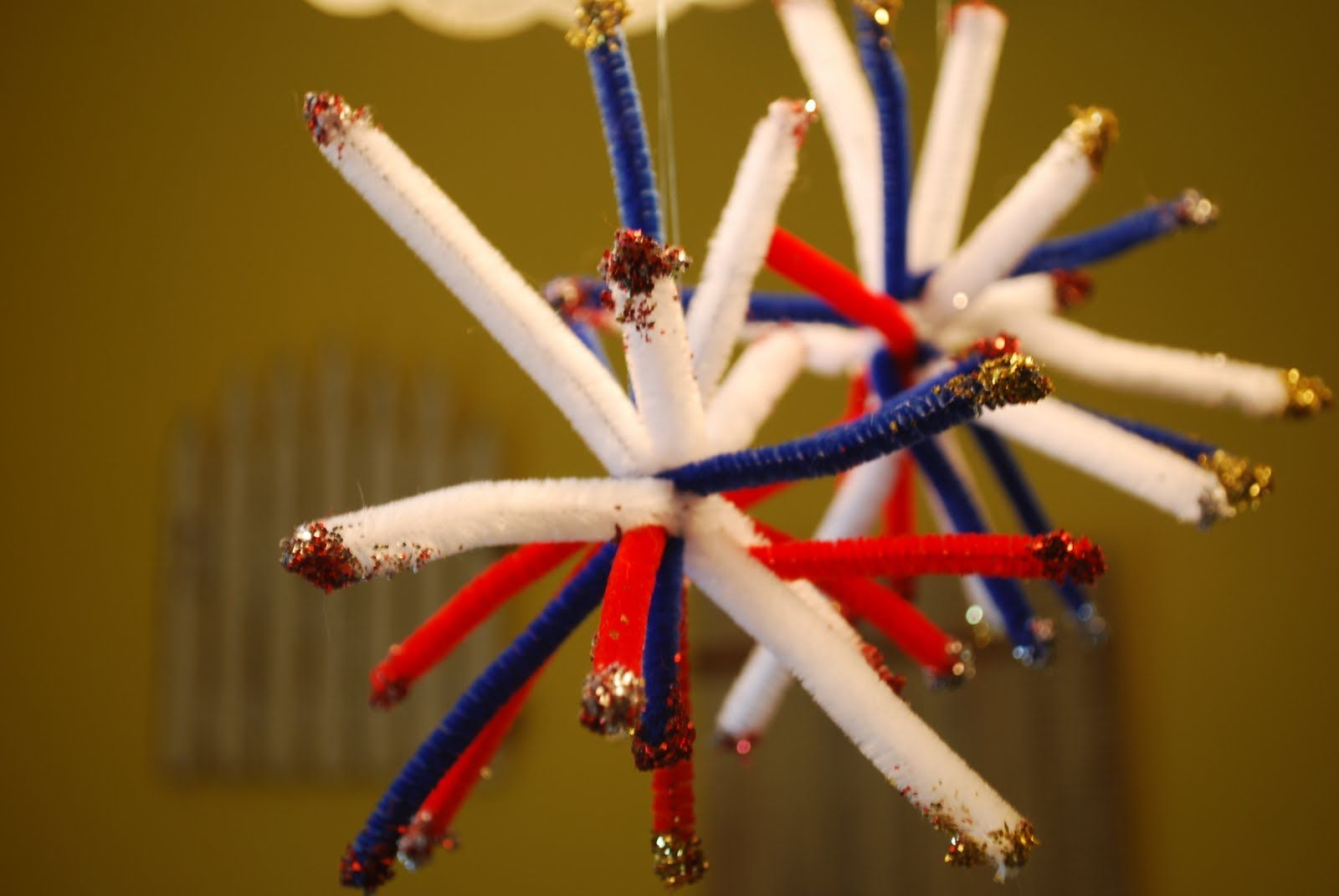 """Dip the ends of pipe cleaners into glue and then into glitter.  Twist one pipe cleaner around the middle of the others to cinch them together.  Fan out to make """"fireworks"""".  Loop thread around one end and hang.  Repeat the phrases """"Oooh"""" and """"Ahhh"""" over and over"""