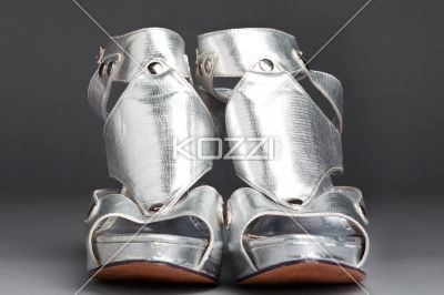 pair of silver high heel shoes. - Pair of silver high heel shoes on grey background.