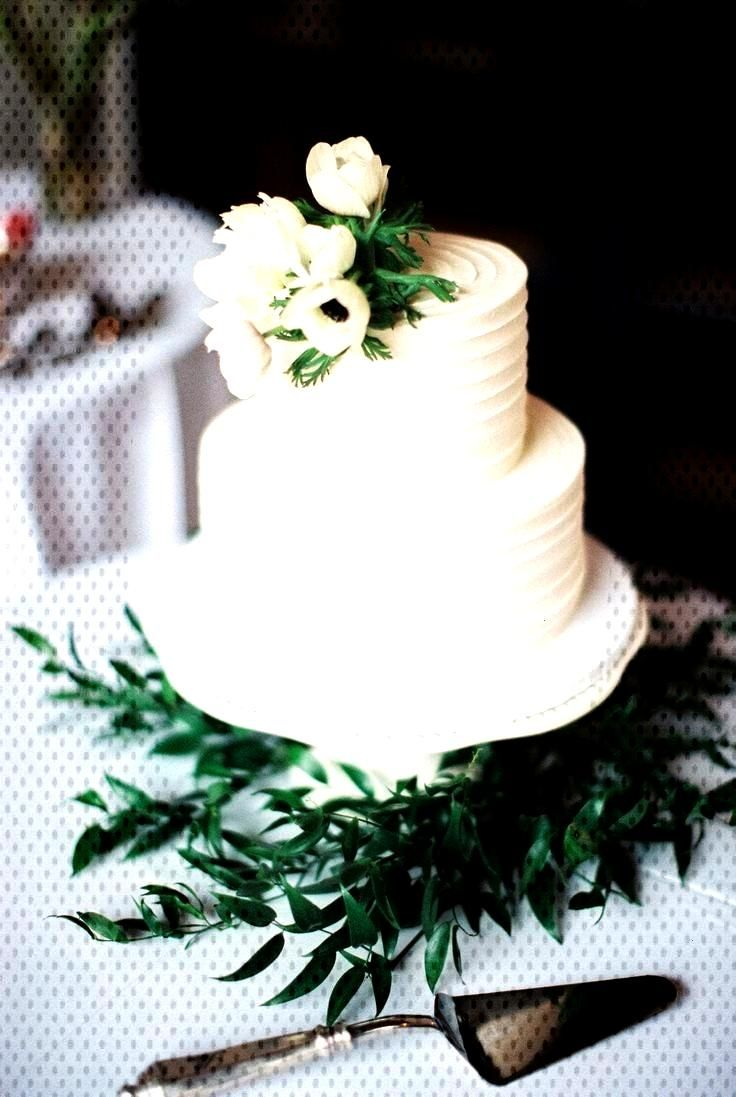 Two tier white wedding cake with greenery and white flowers.