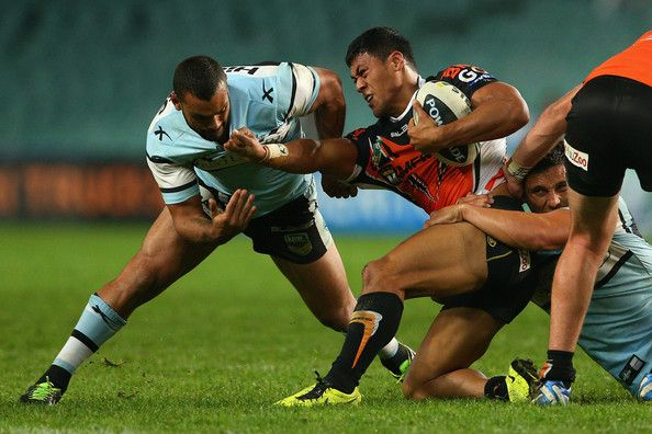 Tim Simona of the Tigers is tackled during the round nine NRL match between the Wests Tigers and the Cronulla Sharks at Allianz Stadium on May 10, 2013 in Sydney, Australia.