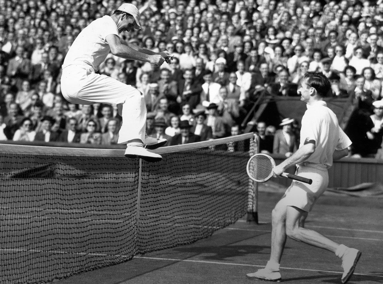 French tennis player Yvon Petra jumps the net at Wimbledon after ...