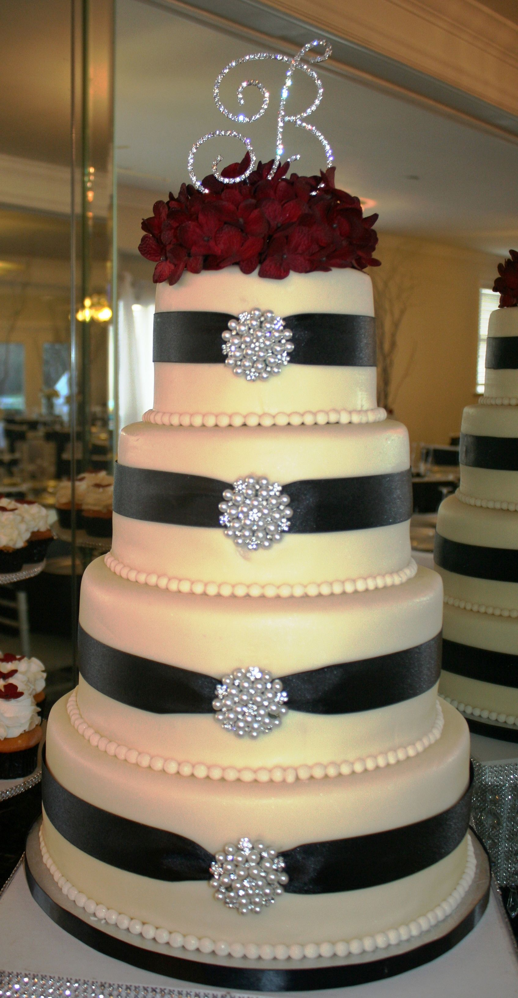 Classic wedding cake, adorned with ribbon & broaches, and topped ...