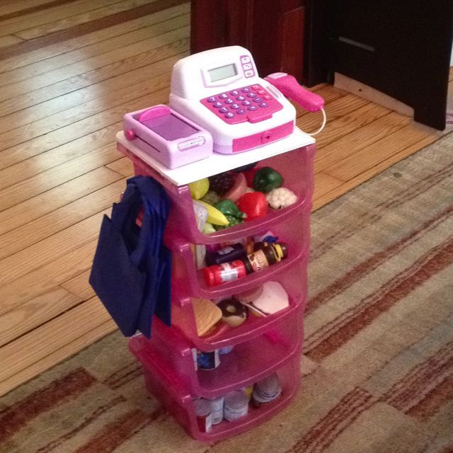 DIY toy grocery store for around $10! 5 dollar tree bins hot glued together, foam board top trimmed to fit and hot glued, cash register on sale at Walgreens ($5), a hook, and some craft bags! We already had the plastic food.