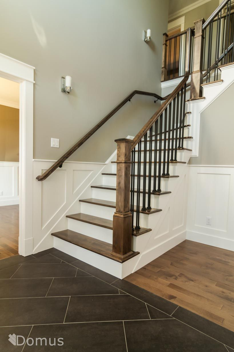 Staircase with white accents and black metal spindles ...