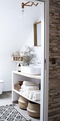 Ein hübsches weißes Badezimmer mit Deko-Körben und Holz-Akzenten