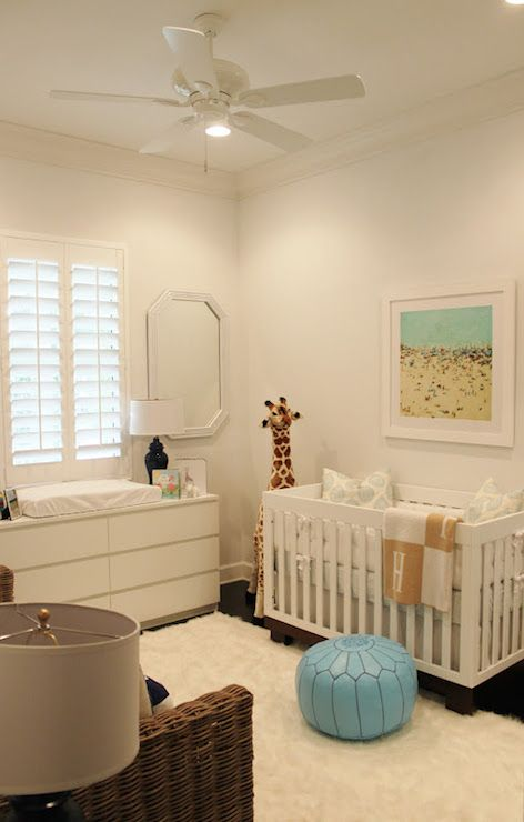 Chic Nursery Features A Ceiling Fan Over An Aerial Beach Photograph Placed White Crib Dressed In And Beige Hermes Style Blanket Next To