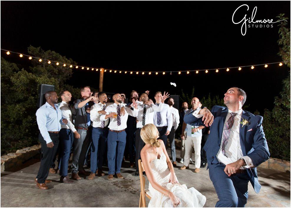 Garter Toss | bride & groom, groomsmen, string lights, blue suit ...