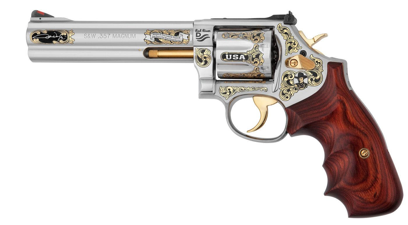 Smith  Wesson Model 686 Plus Revolver in caliber .357 Magnum. This popular 7-shot stainless steel revolver provides the perfect canvas for patriotic artwork honoring the USA and John Wayne, an American legend and proud ambassador for our country. All artwork is featured in stunning 24-karat gold with blackened patina highlights.