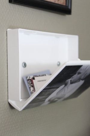 At last, a practical use for those plastic VHS tape boxes! A repurposed box does double duty here:First, as wall-mounted storage, and second, as display space for a photo. Clever -- and useful!