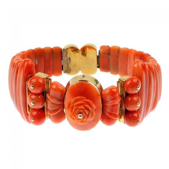A late 19th century carved coral bangle, the front designed as a carved coral flower with coral side detail, to the graduated coral panel bracelet and push-piece clasp.