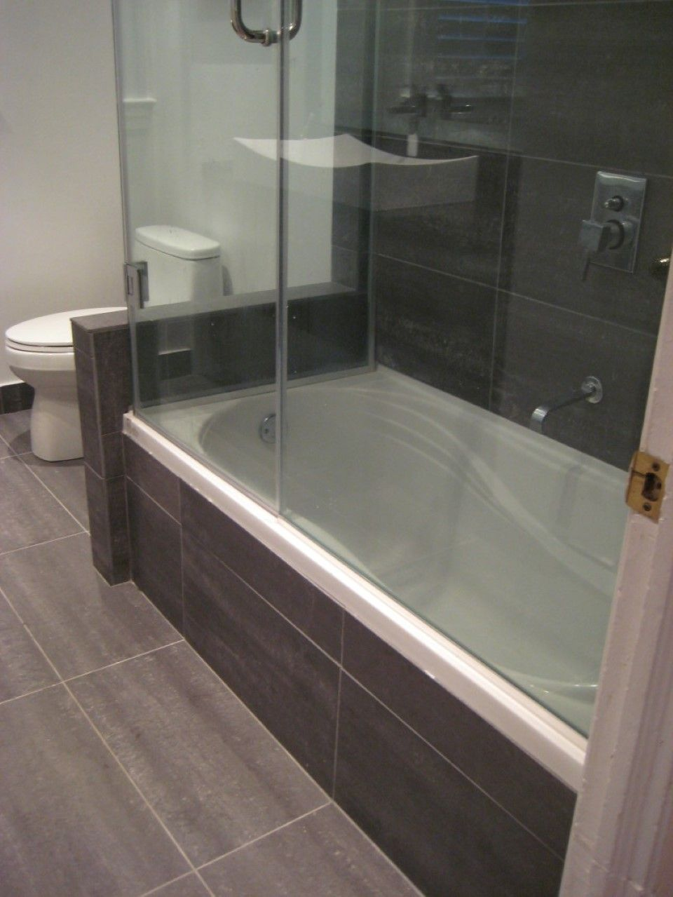 Black bathroom with wooden pattern tiles carrying drop in bathtub with shower also glass Glass bathroom design ideas
