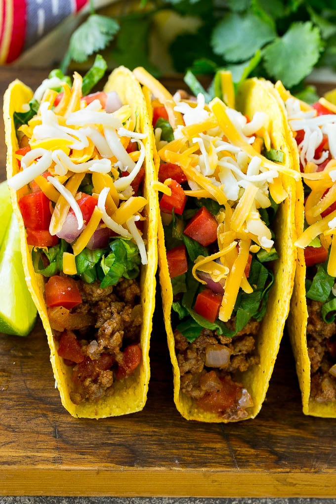 Ground Beef Tacos In Hard Taco Shells Topped With Shredded Cheese Lettuce Tomato And Onion In 2020 Taco Dinner Taco Recipes Ground Beef Ground Beef Tacos