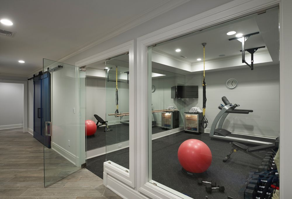 A glass door opens to a basement home gym filled with a mirrored accent wall lined with a corner flat panel tv over a freestanding glass door mini fridge. & Award Winning Outstanding Special Purpose Room | Gym Ideas ... pezcame.com