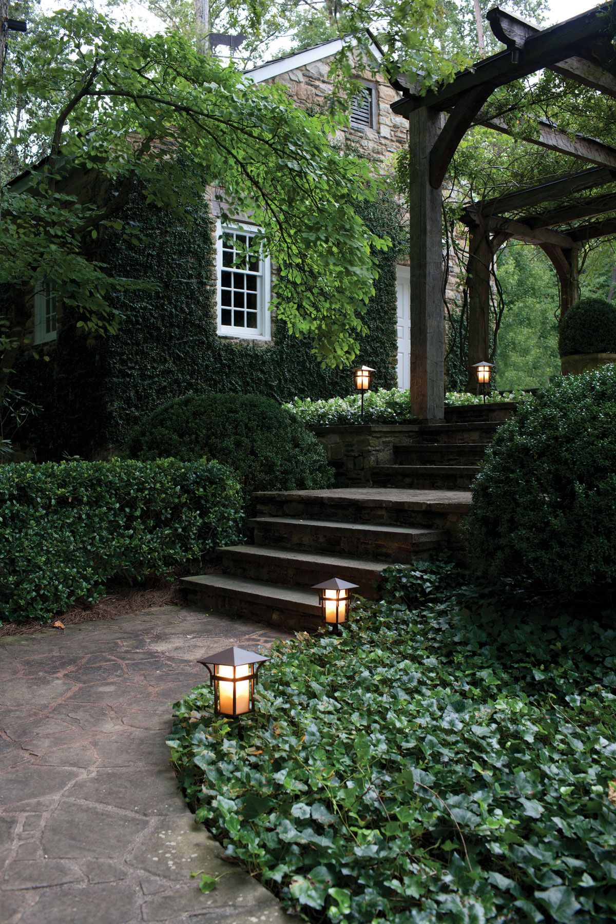 Home garden lights  Path lights and steps leading to elegant pergola with Ivy ground