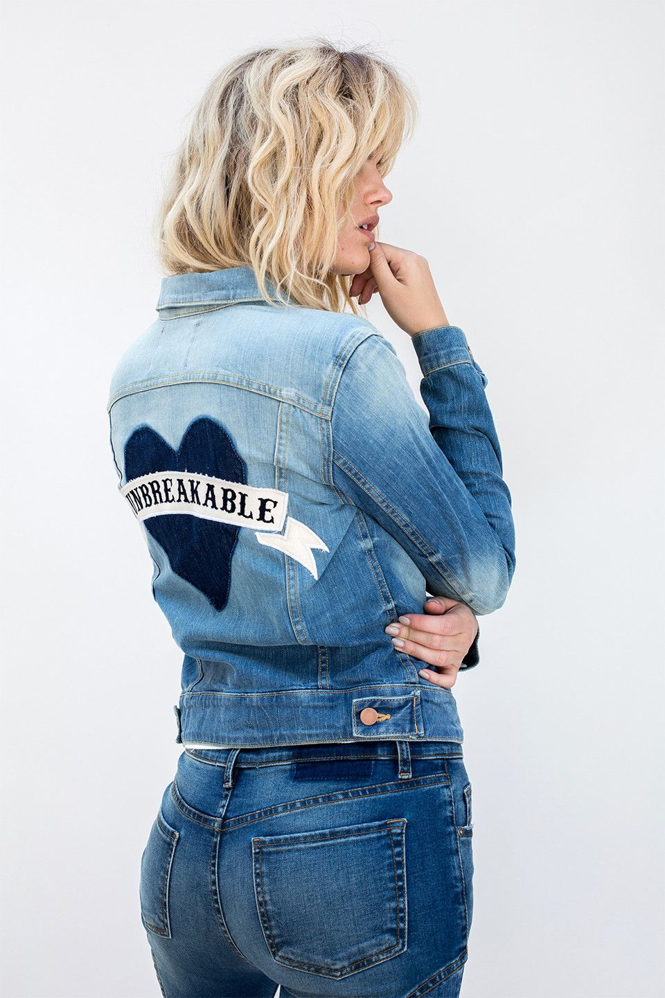 """Be unbreakable with this unique statement denim jacket. Our vintage wash denim jacket featuring a heart shadow patch with embroidered phrase """"Unbreakable"""" on the back was made for you women who want t"""