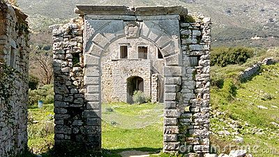 Stone archway with family crest.  This was the entrance to the Old Perithia village school, the ruin of which is seen through the archway.  Taken at the deserted town of Old Perithia, in the foothills of Mount Pantokrator, Corfu, Greece. Old Perithia once had 1200 residents. Some buildings date from 13th Century. The town was abandoned after  earthquake damage.