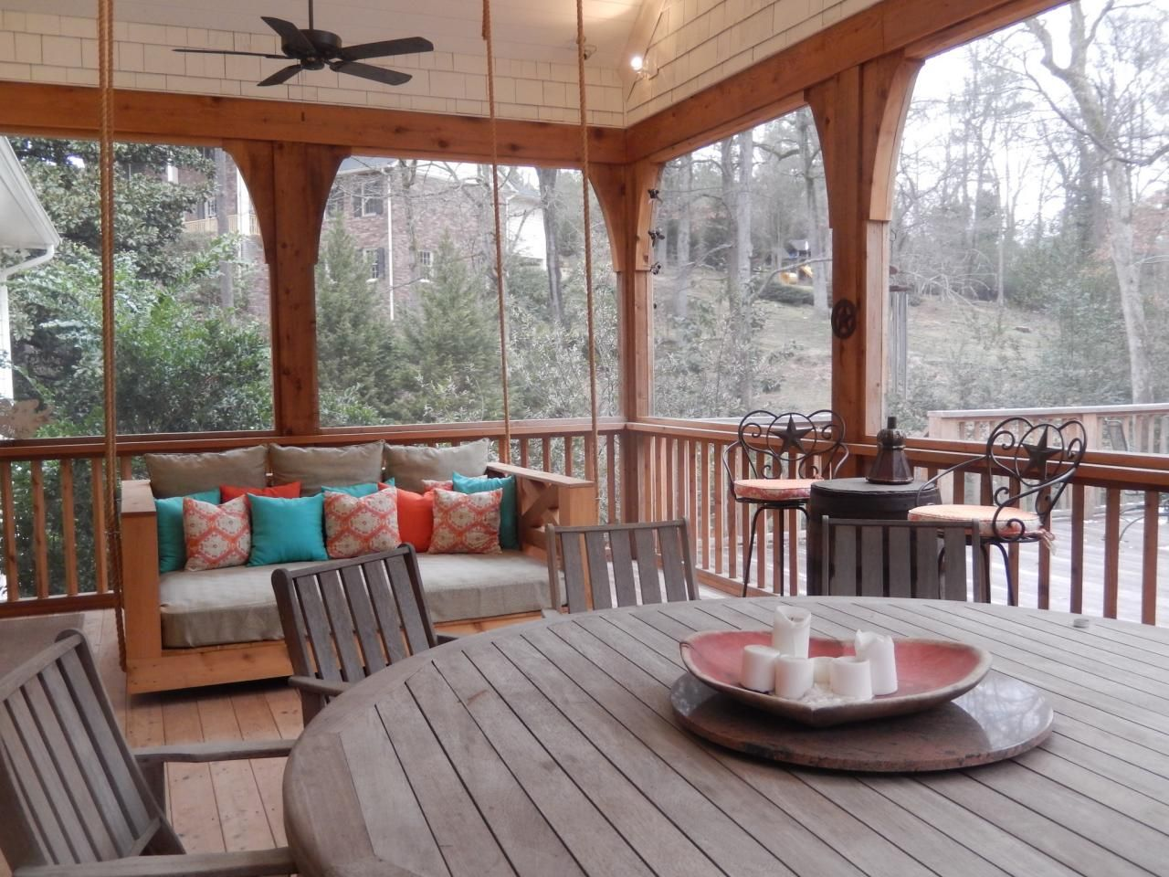 The custom-made bed swing on this Atlanta back porch beckons people to read, chat and nap among the natural surroundings. The swing is one of the homeowners' favorite elements of their outdoor living space.