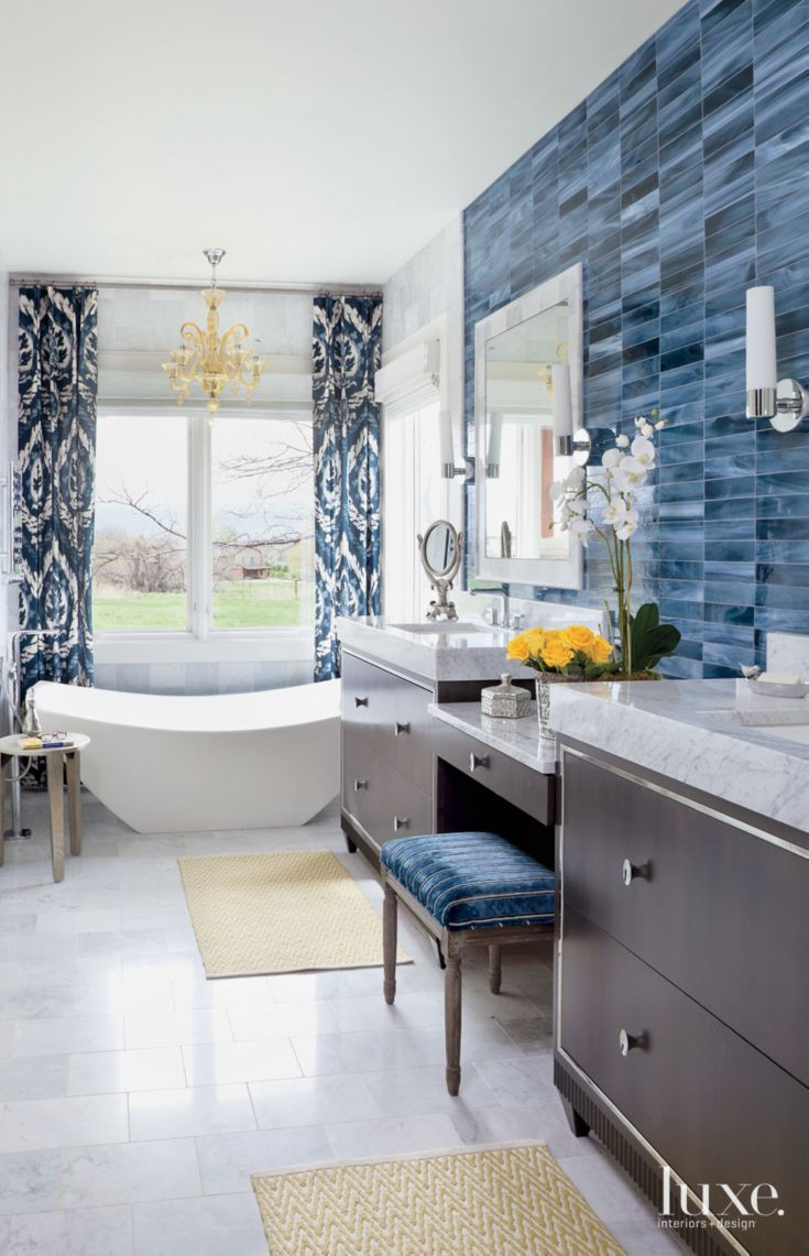 a treviso chandelier by cyan design hangs above this master bathrooms graceful amalfi tub by victoria