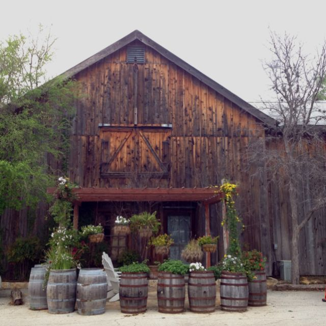 Barn w/ whiskey barrel planters. would be gorgeous for a wedding, just add mason jars and haybales