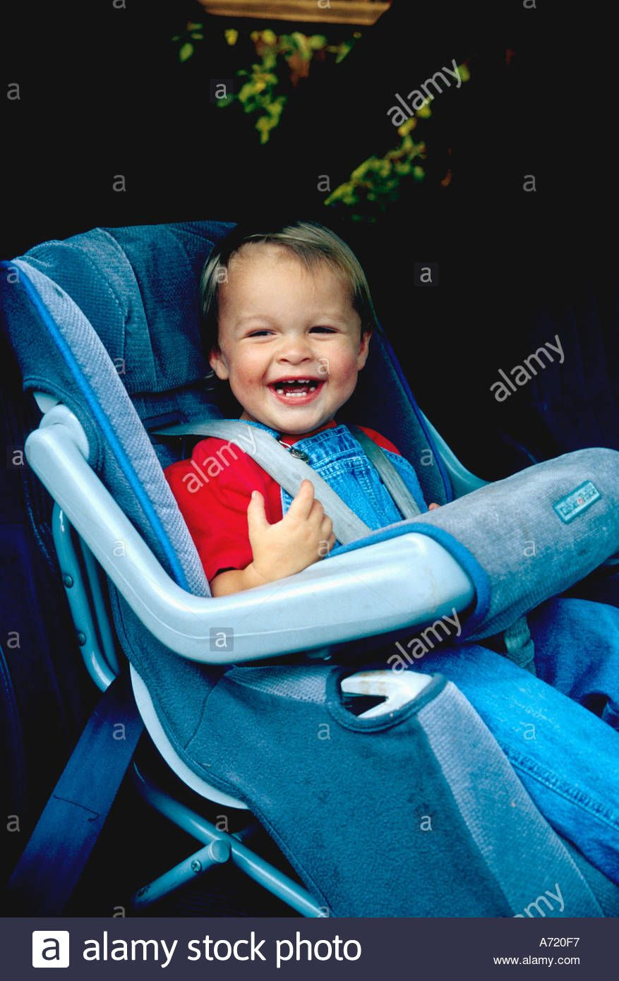 Download this stock image: Infant boy smiling as he has been strapped into  the car seat - A720F7 from Alamy's … | Car seats, Vintage baby gear,  Toddler car seat