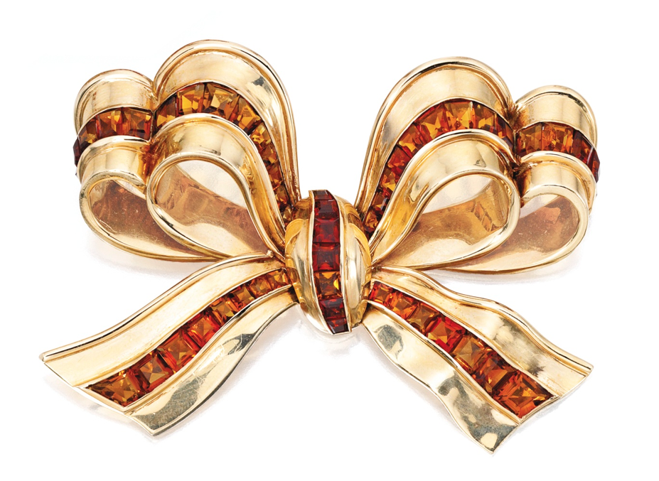 14 KARAT GOLD AND CITRINE BROOCH Designed as a bow accented by numerous calibré-cut citrines, gross weight approximately 25 dwts; circa 1940.