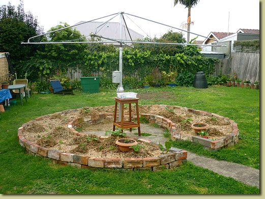 Keyhole garden bed under the backyard clothesline. A ...