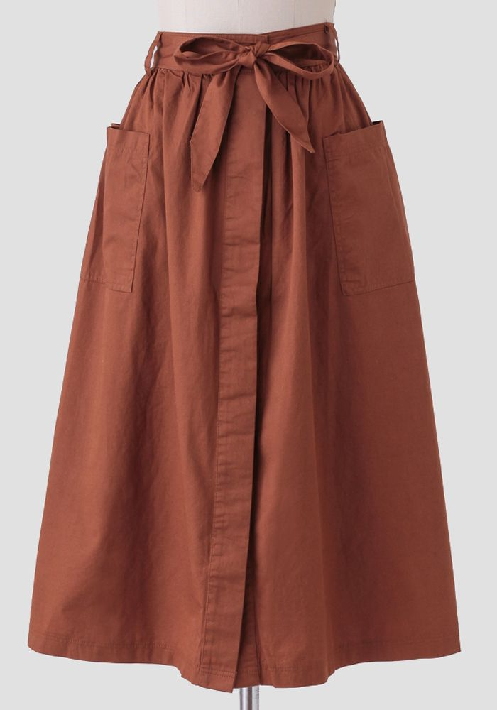 0950e0473 We adore this darling rust-brown colored midi skirt crafted in soft cotton  and featuring two front pockets.